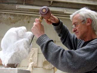 Le Sculpteur Pétrus dégrossit un bloc de gypse pour créer un couple.