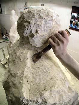 L'artiste taille dans la pierre les épaules de la statue