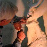 L'artiste sculpte les détails d'une figure du groupe (l'enfant).