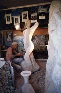 L'artiste sculpte des détails de la statue, partie du monument A ses pieds et autour de lui, une multitude de gravats...