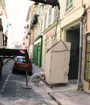 Le sculpteur place des rouleaux en acier sous le bloc pour pouvoir le déplacer et le rentrer dans l'atelier