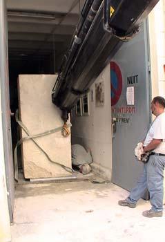Le transporteur de la société Foselev actionne le bras de la grue pour pousser la pierre pendant que le Sculpteur surveille la bonne position des rouleaux d'acier pour assurer l'équilibre et la direction du bloc.