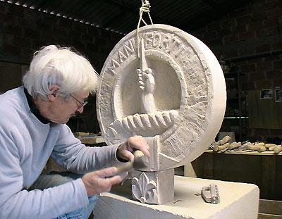 L'artiste sculpte en taille directe un blason en pierre