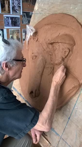 Le sculpteur modèle l'oreille du bas-relier