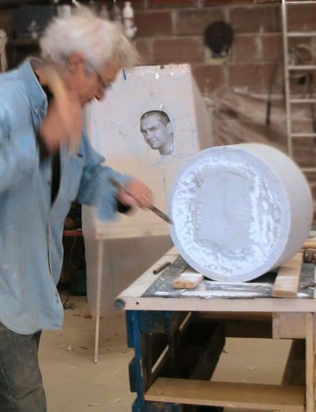 L'artiste dégrossit le bloc de marbre